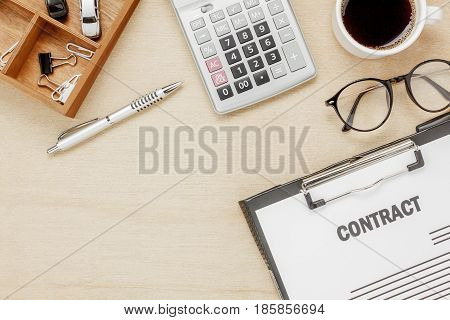 Top view business contract form with coffee eyeglasses car calculator pen with on wooden background.