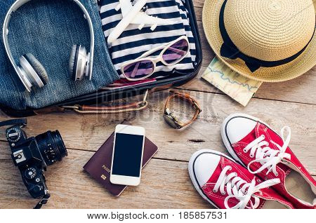Clothing traveler's Passport wallet glasses smart phone devices on a wooden floor in the luggage ready to travel.