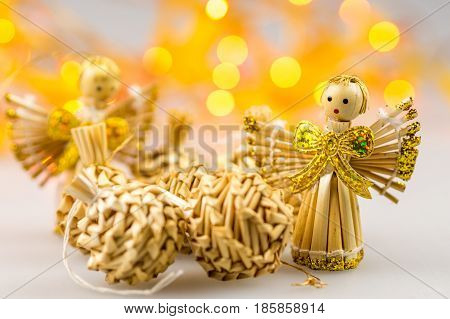 six straw christmas balls and two angels on white background with blurred yellow christmas lights