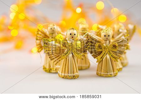 six straw christmas angels on white background with blurred yellow christmas lights