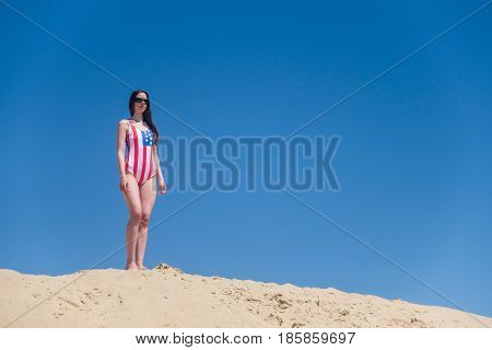 Beautiful young patriot USA on blue sky background in a swimsuit.
