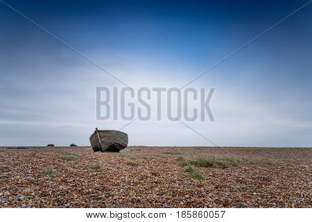A solitary fishing boat on a deserted pebble beach against a cloudy sky