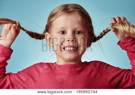 Portrait of joyful girl with pigtails posing in studio over blue background. Happiness and childhood.