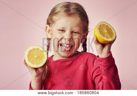 Little girl holding lemons and showing sour grimace.