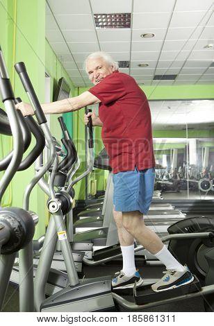 Senior man uses elliptical cross trainer in gym