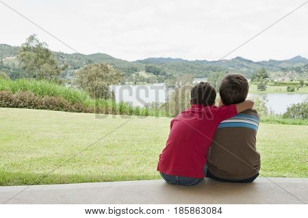 Hispanic boys hugging and looking at view
