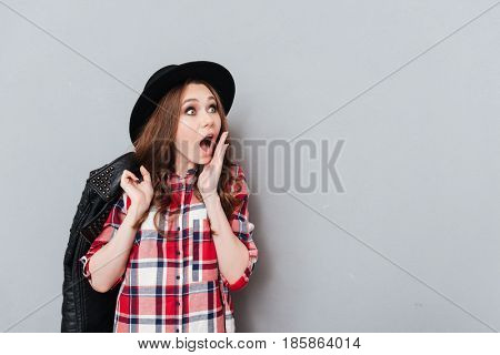 Portrait of an astonished amazed girl in plaid shirt and hat looking away at copyspace isolated over gray background