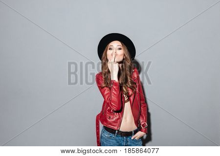 Image of young angry woman standing over grey wall wearing hat showing middle finger. Looking at camera.