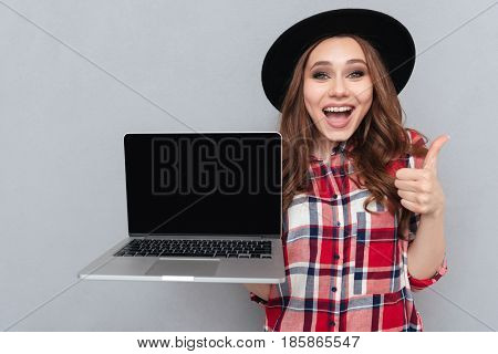 Portrait of a smiling happy girl in plaid shirt holding blank screen laptop computer and showing thumbs up gesture isolated over gray background