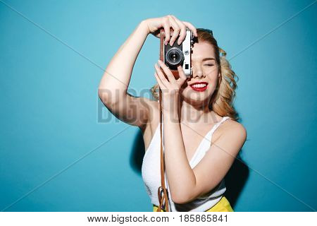 Portrait of a smiling pretty blonde woman in summer clothes taking photo on retro camera isolated over blue background
