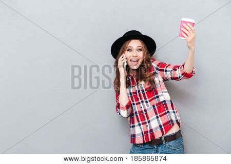Portrait of a smiling excited casual girl talking on mobile phone and holding cup of coffee to go isolated over gray background