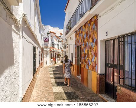 young women walking through pueblo blanco, Andalusia, Spain during hot summer day