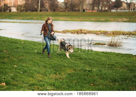 A beautiful girl is walking along the embankment. Blond hair and brown jacket. Spring.