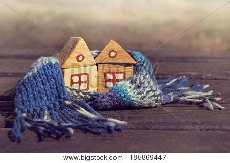 Couple of small wooden house in a warm blue scarf/ Warming atmosphere for living together