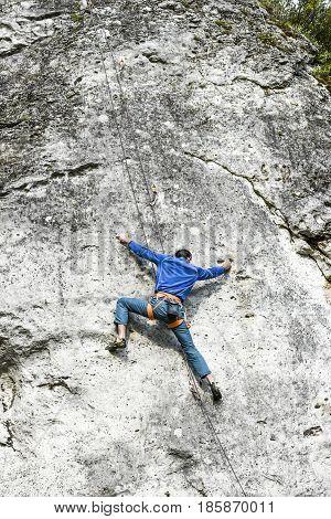 Podlesice Poland april 30 2017: Young male climber climbing a route on a rock. Jura krakowsko chestochowska.
