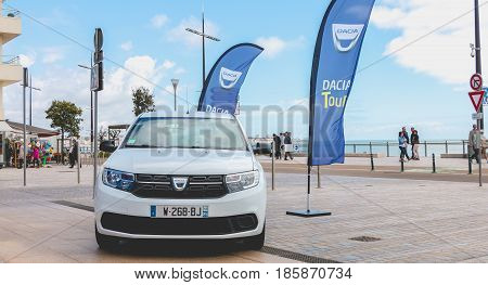 Sables d Olonne France - May 07 2017 : Dacia Tour 2017 is a commercial operation organized by the car builder in order to present its cars throughout France - A young man watching a car