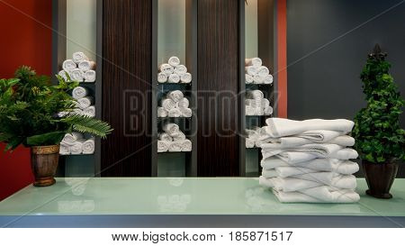 Stack of clean towels on wooden bench in fitness club