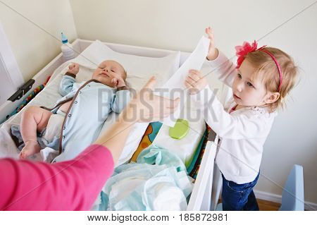 Lifestyle portrait of cute girl toddler helping her mother changing baby diaper. Older sister looking at her little younger sibling brother.