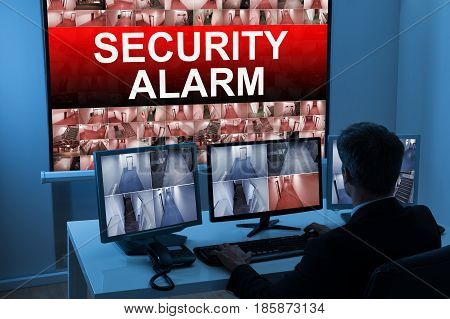 Male Operator Monitoring Multiple CCTV Footage With Security Alarm Text On Screen