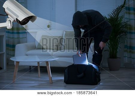 CCTV Camera Showing A Burglar Stealing Things In The House At Night