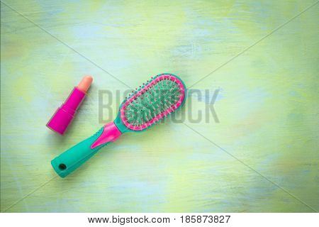 Green and pink hairbrush lipstick on a light wooden background