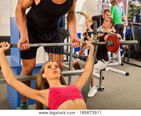 Fitness friends workout gym. Woman working on bench press. She lifting barbell. Trainer backs girl while taking exercises. Girl breathes deeply and heavily. Group work people on treadmill background.