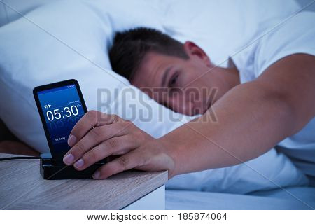 Close-up Of A Man Waking Up With Alarm On Mobile Phone