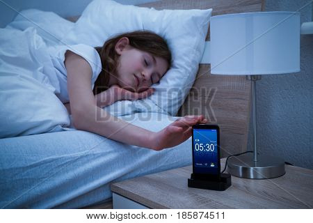 Close-up Of A Sleepy Girl Snoozing Alarm On Smartphone