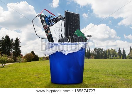 Damaged Hardware Equipment In Blue Dustbin On Lawn