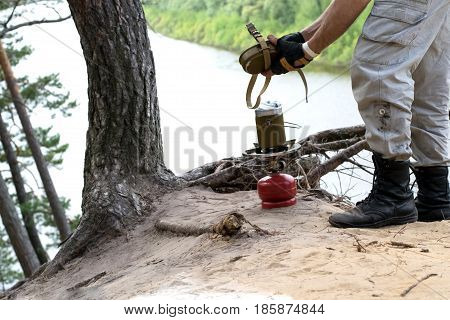 Traveler in leather boots prepares for a gas burner food over cliff above the river
