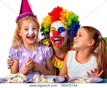 Birthday children clown eating cake with two girl together. Kids with messy face have tier cake fight on isolated. Fun happy childhood of small group people. Children play with a clown.