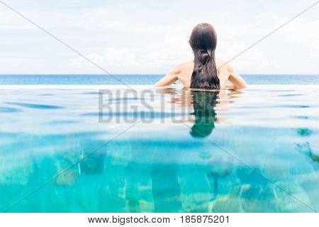 Woman tourist in infinity pool of hotel resort enjoying the view over the ocean