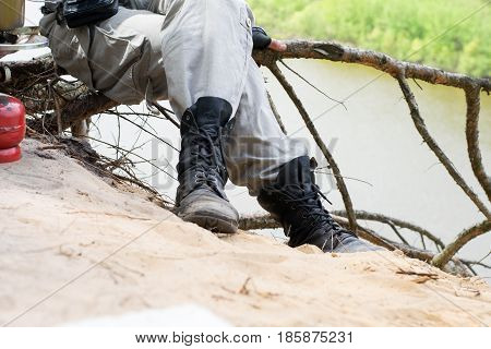 Traveler in leather boots sit over a cliff above river near gas burner