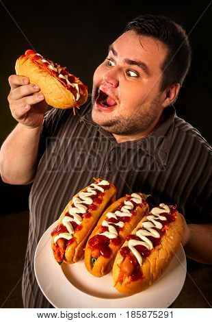 Diet failure of fat man eating fast food hot dog on plate. Breakfast for overweight person who spoiled healthy food. Junk meal leads to obesity. Enraged by a large amount of food fat.