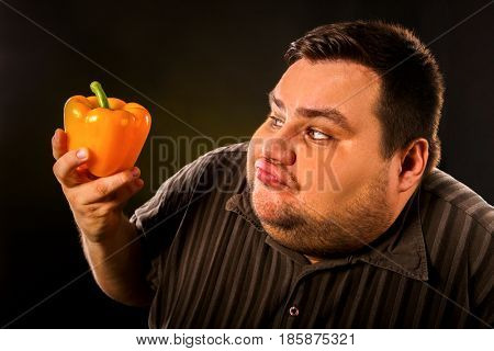 Diet fat man eating healthy food . Health breakfast with vegetables cauliflower and sweet pepper with radish for overweight person. Caricature of a fat man.