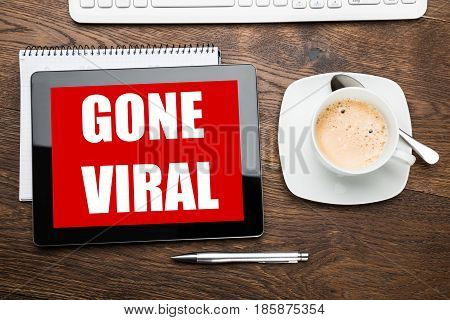 Elevated View Of A Coffee With Digital Tablet Displaying Gone Viral Text On Wooden Desk