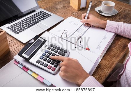 Businesswoman Calculating Tax Using Calculator On Desk In Office