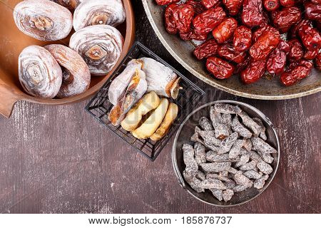 Dried fruits - persimmon figs red dates or jujube and salted sliced plum. Top view.