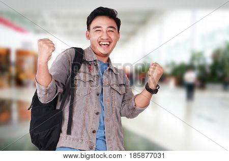 Photo image portrait of a successful cute young Asian male student smiling and showing winning gesture half body close up portrait
