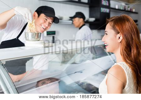 Laughing young Asian man serving a pretty woman weighing cheese at a delicatessen counter with a friendly smile