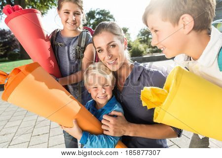 Woman and kids at enrolment day with school cones