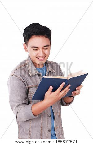 Photo image portrait of a cute young Asian male student standing and smiling while reading a book isolated on white