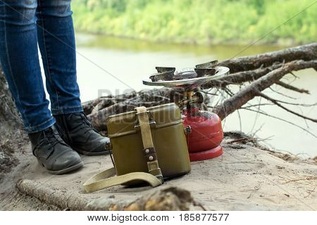 Traveler in leather boots stay over a cliff above river near gas burner