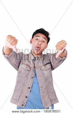 Photo image portrait of a cute young Asian man doing mocking gesture with tongue out and showing two thumbs down isolated on white