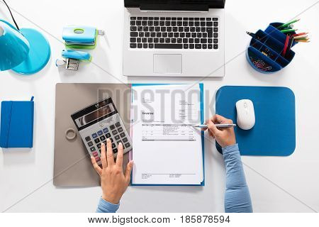 Elevated View Of A Businesswoman Calculating Invoice Using Calculator