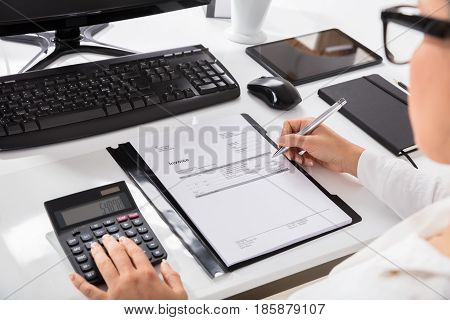 Close-up Of A Woman Calculating Invoice Using Calculator On Desktop At Workplace