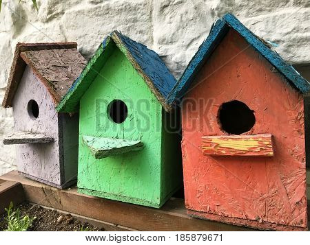 Three funny color birdhouses on the street