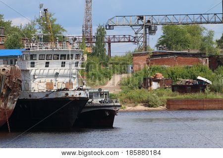 River bay with rusty cargo ships on sunny day ship bows industrial area