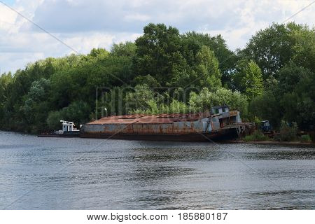 River watrer lonely rusty cargo ship dire straits among bushes on summer day