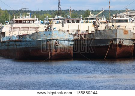 River bay with rusty cargo ships on summer day ships bows with anchors
